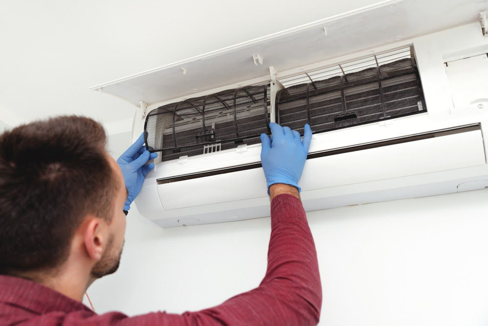 Dilling heating and air specialist replacing air filter as part of maintenance plan